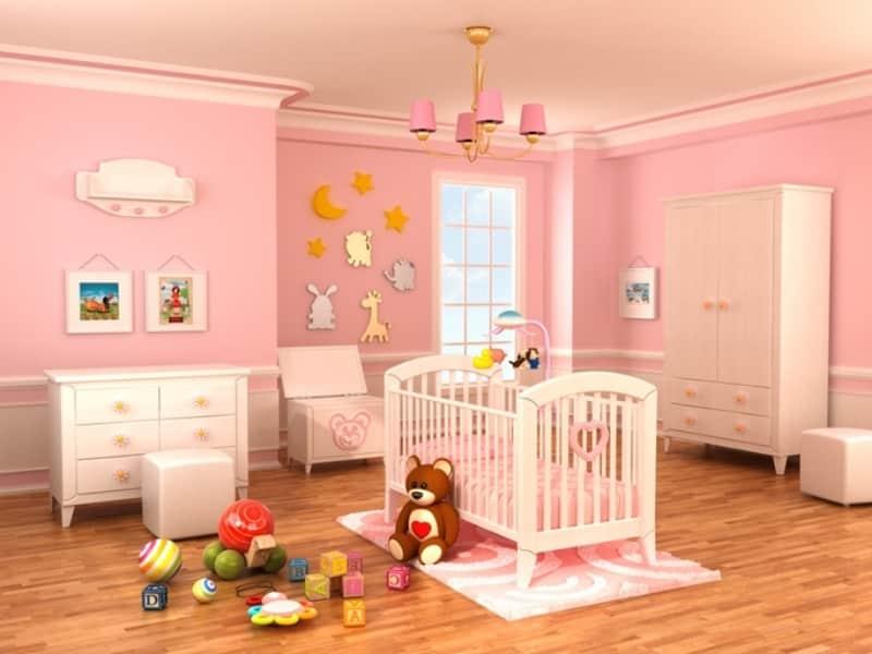 Quarto de bebê com parede rosa e piso de madeira