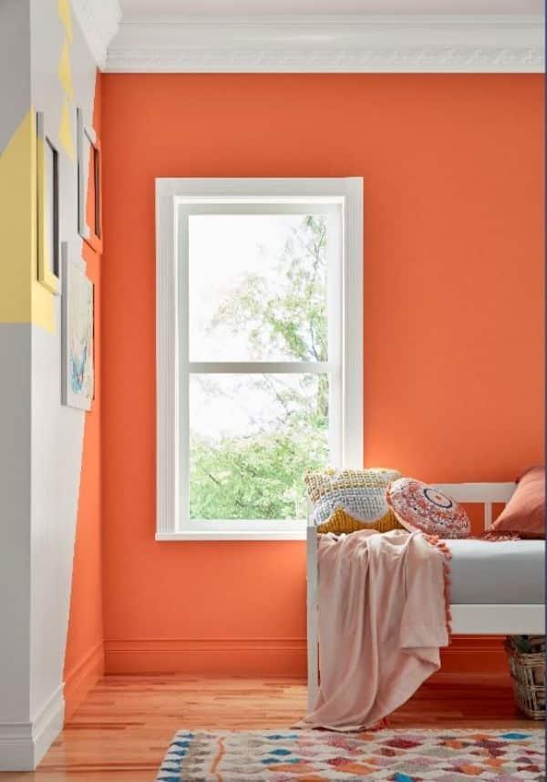 Quarto decorado com parede laranja com branco