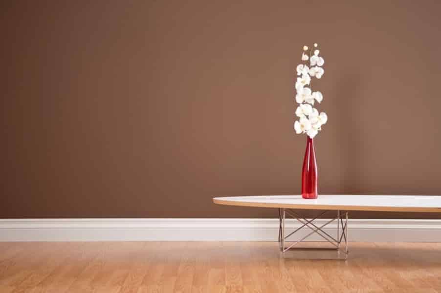 Sala com parede marrom e piso em madeira