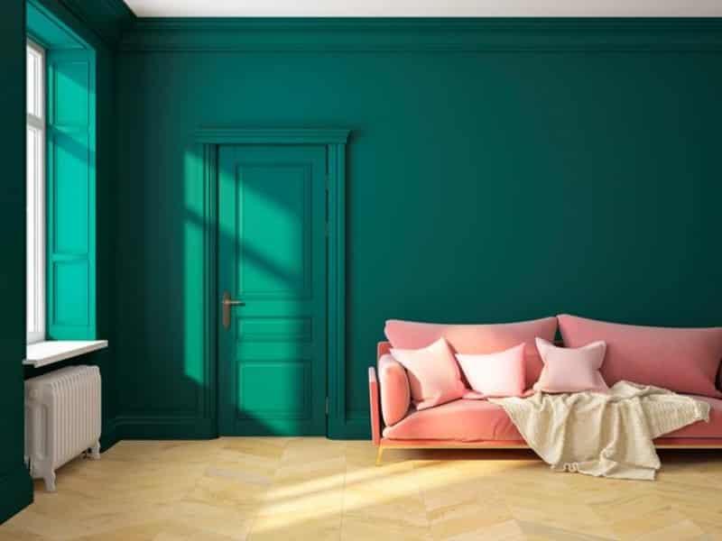 Sala com parede verde escuro e piso em madeira clara