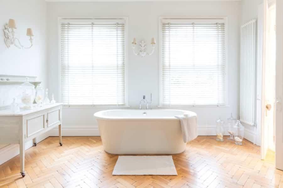 Banheiro branco com madeira branca.