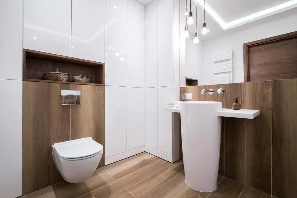 Banheiro branco com piso de madeira.