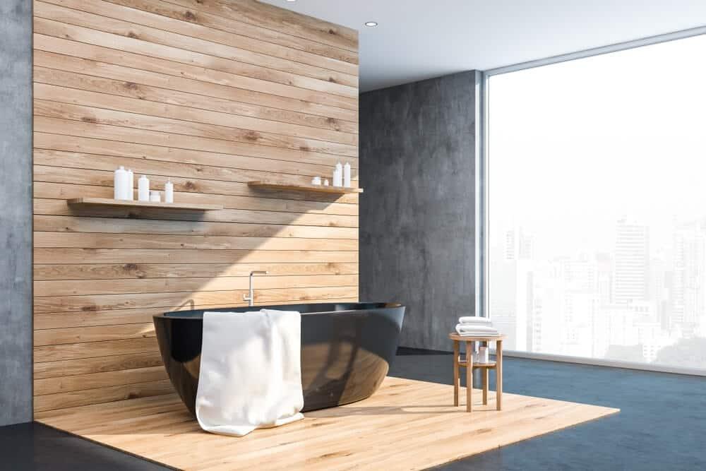 Banheiro cinza com piso de madeira em pequeno espaço.