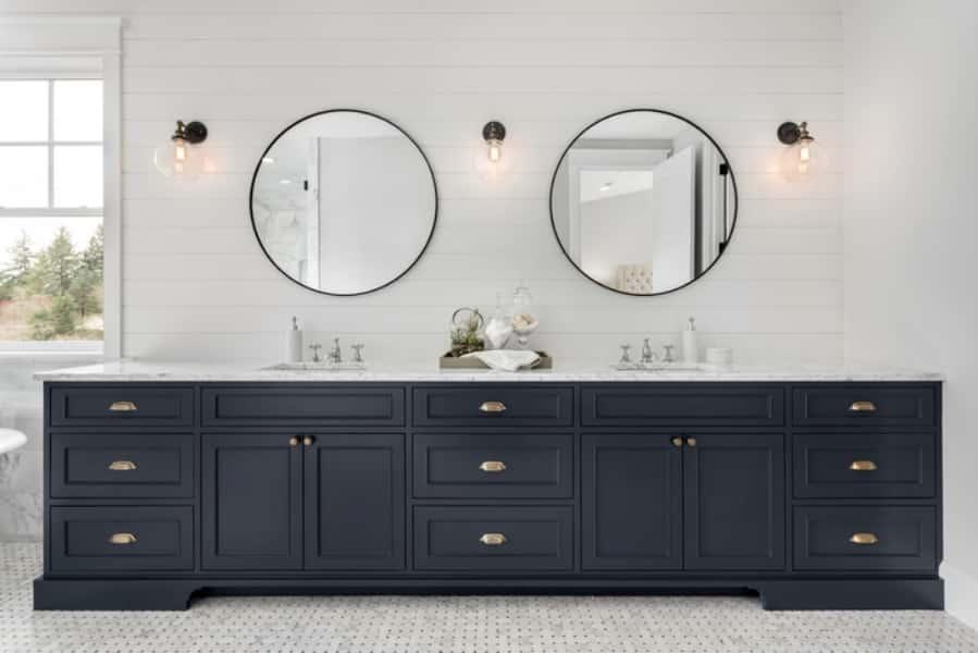 Banheiro com três arandelas e dois espelhos.