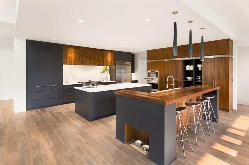 Cozinha cinza com branco e piso de madeira clara.