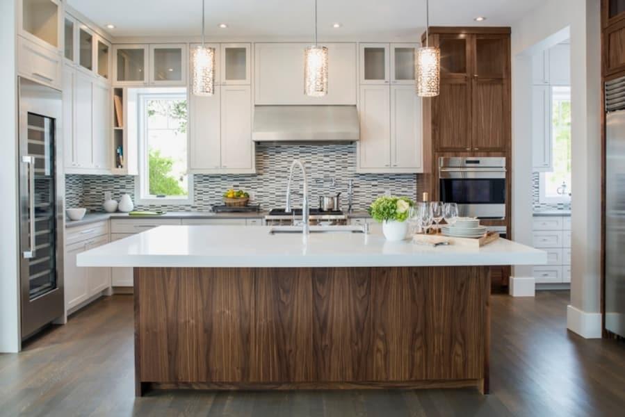 Cozinha com bancada branca e piso de madeira escuro.