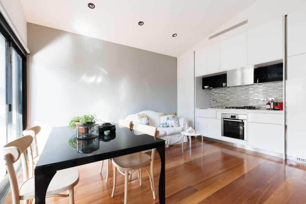 cozinha com mesa preta e sofá branco - Como projetar um espaço aberto em um pequeno espaço?
