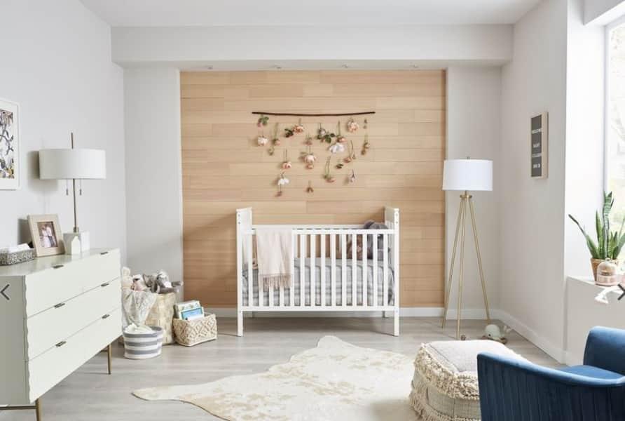 Quarto de bebê com parede destacada estilo madeira.