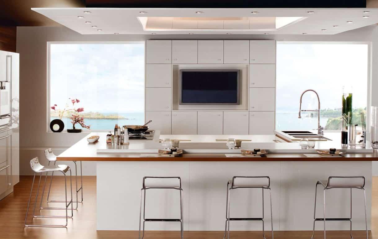 Cozinha com bancada de madeira e cadeiras cromadas.