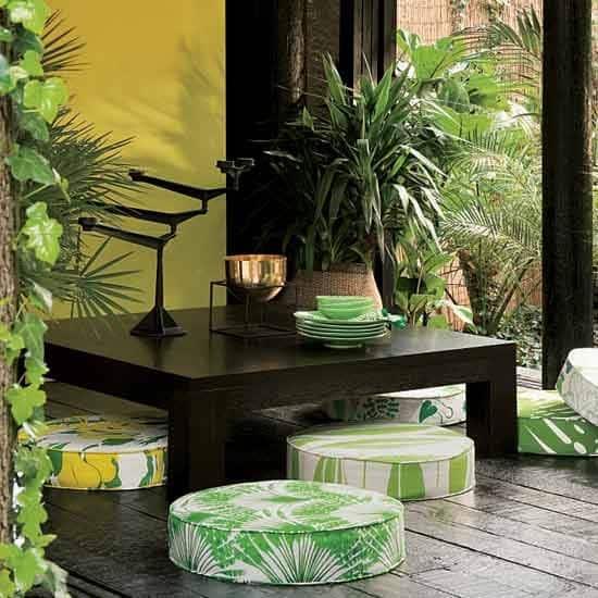Espaço com mesas preta e plantas.