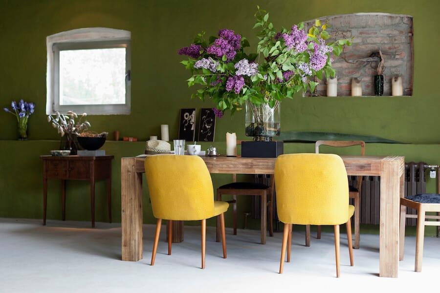 Espaço com paredes verde escuro e cadeiras amarelas.