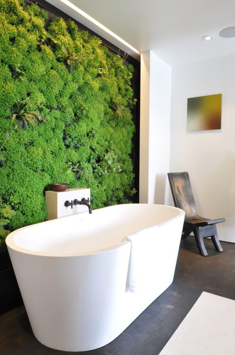 Banheira branca com parede de vegetação.