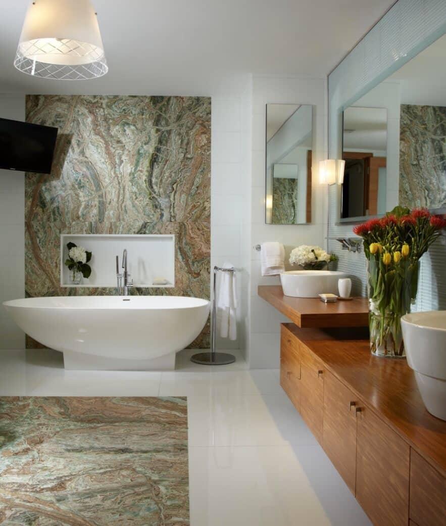Banheiro com parede e piso de pedra natural.