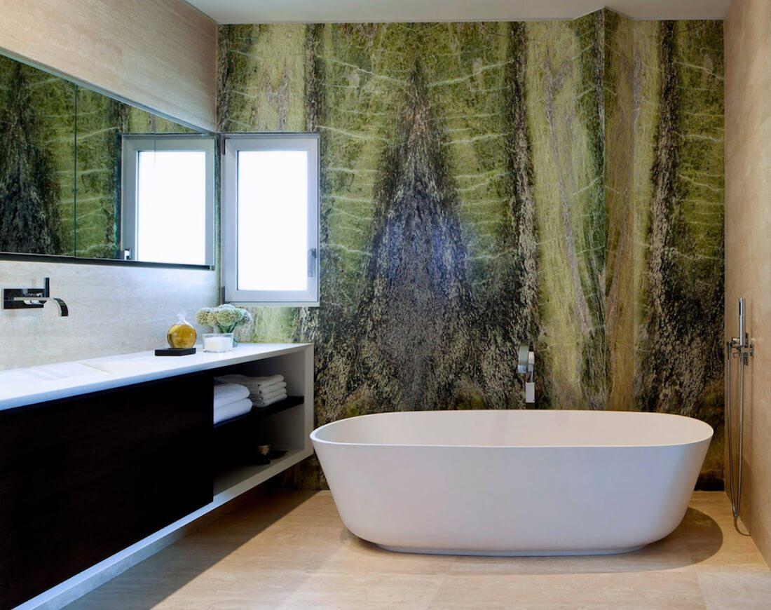 Banheiro com parede em mármore verde colorido.