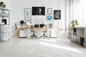 Escritório todo branco com quadros na parede.