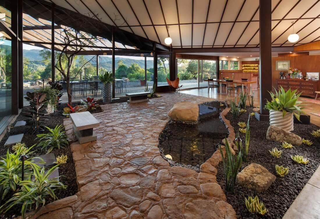 Espaço interno com jardim e chão de pedra.