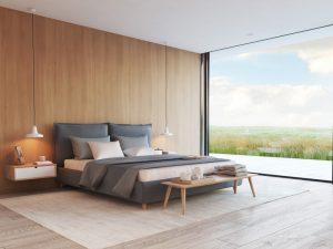 Quarto com cama cinza e parede de fundo com textura de madeira.