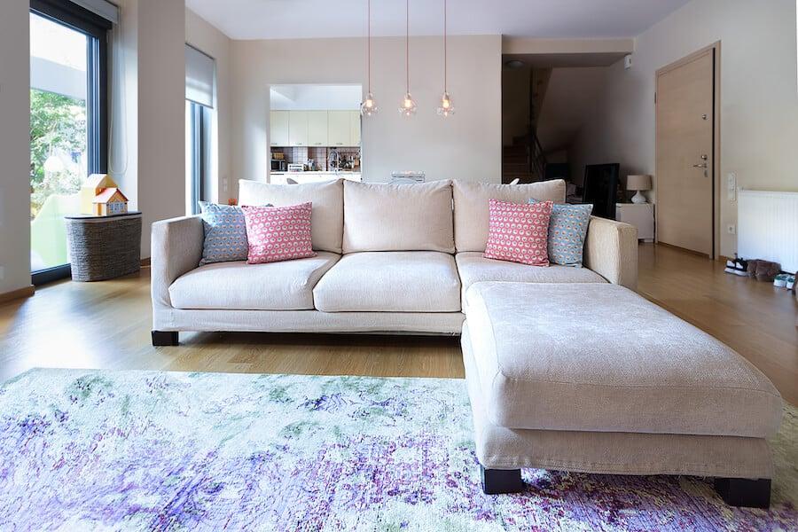 Sala com piso de madeira e sofá claro