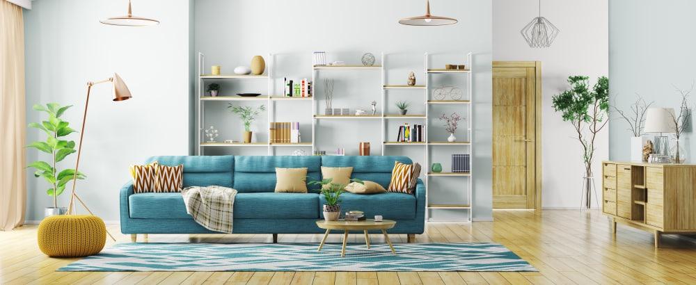 Sala com piso de madeira clara e sofá azul.