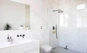 Banheiro branco com box de vidro transparente.