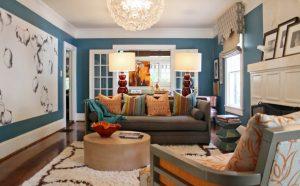 Sala de estar azul e branco e sofá cinza com almofadas coloridas.