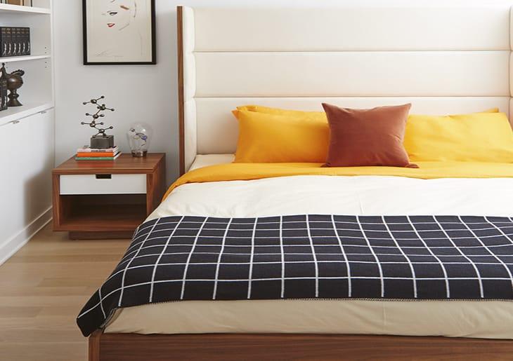cama com cobertas listrada branca e amarelo escuro - Quando usar Feng Shui no seu quarto de acordo com um especialista