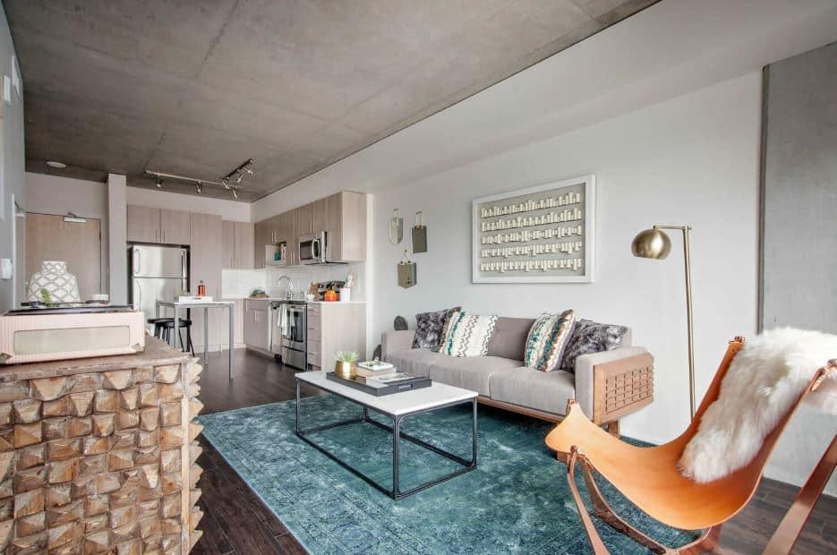 Sala com uma bancada de pedras e um sofá cinza - Ideias de layout para apartamentos tipo Studio