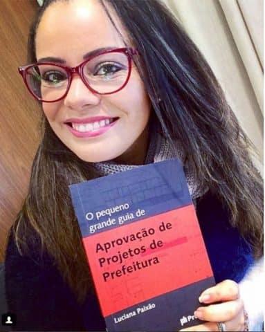 """Luciana Paixão segurando o livro """"O pequeno grande guia de aprovação de projetos de prefeitura"""""""